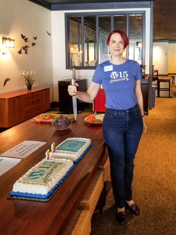 Sallie Goetsch poses with a kitchen knife by the #wp15 cakes